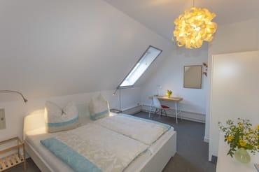 Schlazimmer 2 mit Doppelbett und Schreibtisch