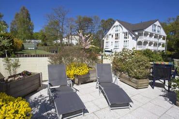 Terrasse mit Sonnenliegen und Gartenstühle