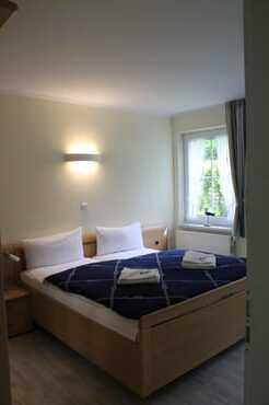 Schlafzimmer mit Doppelbett und Zugang zum Duschbad mit WC.