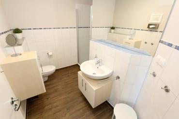Bad mit bodengleicher Echtglasdusche, große Spiegelfront, Handtuchwärmer, viel Stauraum