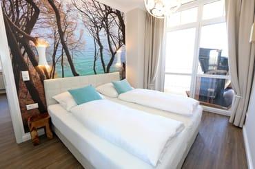 Das Schlafzimmer mit Boxspringdoppelbett, zusätzlichem TV, Verdunklungsvorhängen, transparenten Plissees und großem, geräumigen Kleiderschrank