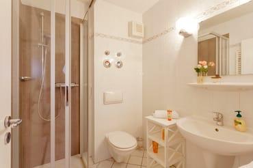 Das Bad ist mit moderner Dusche, ...