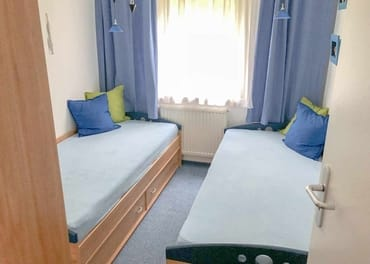 Das Schlafzimmer mit Einzelbetten und Kleiderschrank