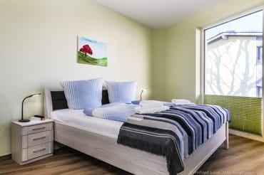 Schlafzimmer 1 mit Doppelbett, Nachttisch mit Leselampen