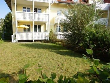 Balkon / Terrasse mit gelbem Sonnenschirm und Garten