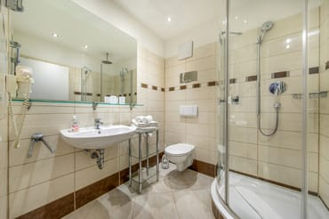Das moderne Bad mit Dusche, WC und Fön.