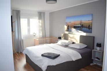 Schlafzimmer 1 mit Babybett und TV