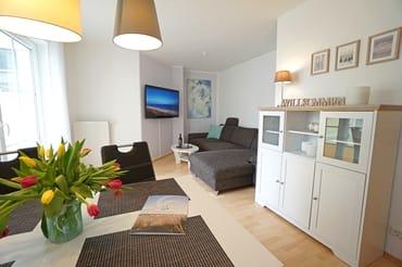 Wohnzimmer mit Schlafcouch und Flachbildfernseher