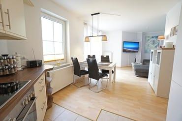Wohnzimmer mit Küchenzeile, Esstisch, Schlafcouch und TV