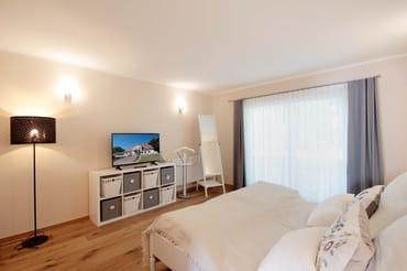 Schlafzimmer mit Doppelbett, zusätzlichem TV und Zugang zur zweiten Terrasse