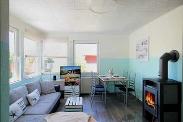 Bungalow teilt sich auf in ein Wohnzimmer mit Kamin und einem Essbereich