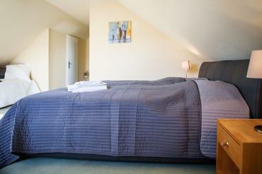 erstes Schlafzimmer mit Doppelbett und Einzelbett