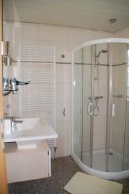 Badezimmer mit Eckrunddusche und Handtuchtrockner über Fußbodenheizung