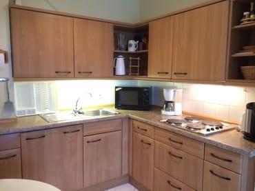 4-Pl.-E-Herd, Kühlschrank, Mikrowelle mit Grill, Kaffeemaschine, Thermoskannen, Wasserkocher, Toaster, Flaschenwärmer, reichlich Geschirr und Kochutensilien