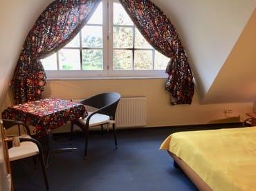 Geräumiges Schlafzimmer mit kleiner Sitzgruppe und Kinderbett (1,20 mal 0,60 m, Holzgitterbett)