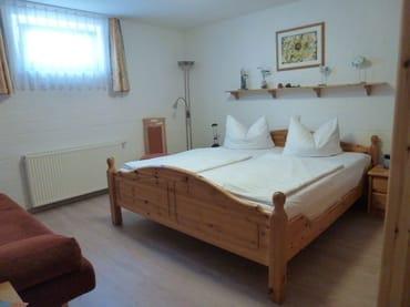 Schlafzimmer mit Doppelbett und Couch
