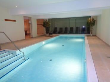 Wellnessbereich mit Schwimmbad und Ruheraum im Hintergrund