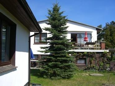 Ferienhaus  (Fenster Wohnzimmer mit Blick in den Garten), im Hintergrund Wohnhaus der Vermieter