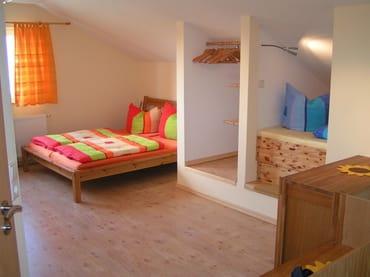 Wohn- und Schlafraum im Obergeschoss mit Doppelbett und eingebautem Alkovenbett (rechts), sehr beliebt bei den Kindern und Leseecke mit CD-Player(nicht im Bild)