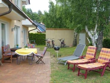 Großzügige, geschützte Terrasse hinter dem Haus, mit schönem Garten und Beleuchtung
