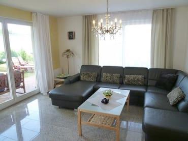 Großzügiges, helles Wohnzimmer mit drei großen Terrassentüren, exklusiver Natursteinboden in der gesamten Wohnung
