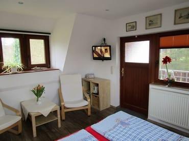 Wohn-Schlafraum mit Sitzecke und Tür zum Balkon