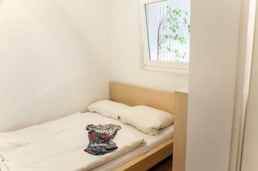 das kleine Schlafzimmer mit dem 160cm breitem Bett. Durch das Fenster schaut man in die Veranda...