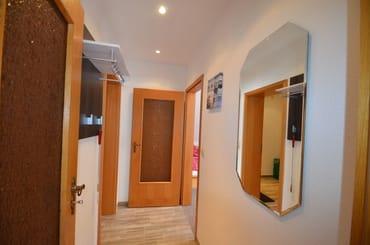 Eingangsbereich des Appartements mit Flurgaderobe, Blick aus dem Bad in die Diele