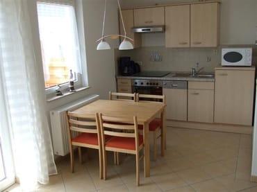Essecke mit komplett ausgestatteter Küchenzeile (z.B. Backofen, Geschirrspüler, Mikrowelle, Kühlschrank mit Gefrierfach, Geschirr usw.)