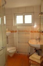 Modernes Badezimmer mit Dusche, ein Handtuchset pro Person