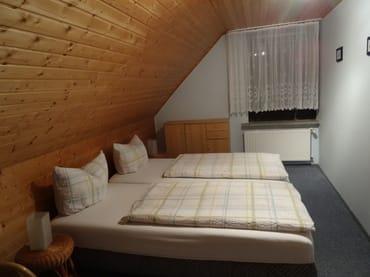 Schlafzimmer mit Doppelbett, Kleiderschrank. Bei Bedarf kann ein Kinderbett zugestellt werden