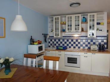 Küchenzeile mit Herd, Kühlschrank, Mikrowelle und Küchengeräten