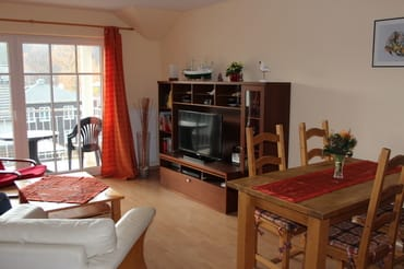 Das Wohnzimmer mit gemütlicher Sitzecke, Fernseher, Blue Ray-Player, Stereoanlage und Zugang zum Balkon sowie Essbereich