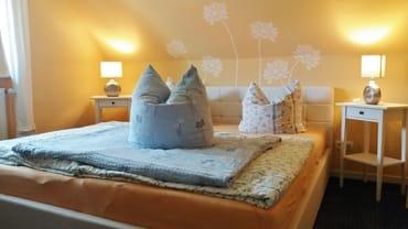 sonniges Schlafzimmer mit Doppelbett