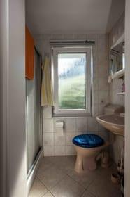 Badezimmer mit Fußbodenheizung,Duschkabine,Waschbecken,Toilette