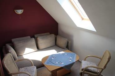 Wohnzimmer mit Schlafcouch und Fernseher