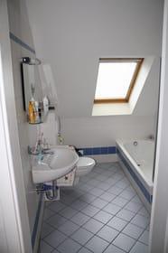 Wannenbad, hinter der Tür eine Waschmaschine, Zugang vom Flur