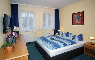 Schlafzimmer mit Doppelbett und Flachbild-TV