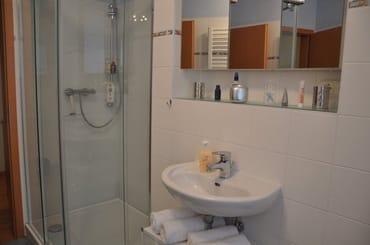 Tageslichtbad mit Ganzglasdusche, Handtuchtrockner, Fön und Spiegelschrank (3-teilig).