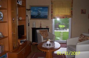 Blick ins Wohnzimmer mit E-Kamin, Tür zur Terasse -Garten