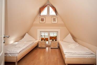 Gemütliches Schlafzimmer im Spitzboden mit Fernseher, besonders beliebt bei den Kindern.reisebett