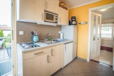 Küchenzeile mit kleinem Geschirrspüler,Kühlschrank mit Tiefkühlfach, Mikrowelle, Kochplatten, Kaffeemaschine, Toaster und Wasserkocher sowie Küchenutensilien
