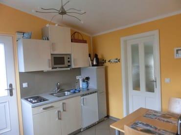 Küchenbereich mit Geschirrspüler, Mikrowelle, Kaffeemaschine, Toaster, Geschirr und Sitzbereich