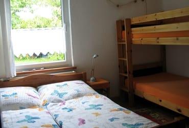 Betten für vier Personen im Schlafzimmer mit Blick zum Garten