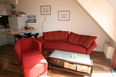 Wohnzimmer mit gemütlichem Sofa, Sessel und Hocker