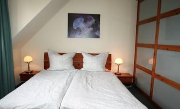 Unteres Schlafzimmer mit Doppelbett und großem Kleiderschrank
