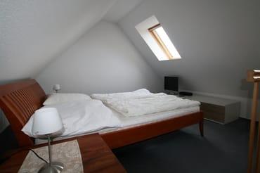 Oberes Schlafzimmer mit Doppelbett und TV