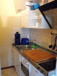 Küchenzeile mit Ceran-Kochfeld, Kühlschrank, Backofen, Geschirrspüler, Toaster, Wasserkocher und Kaffeemaschine
