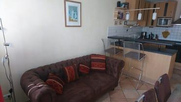 Wohnzimmer mit Couch und offener Küche
