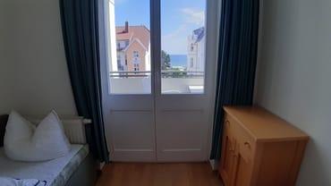 kleines Schlafzimmer mit Zugang zum Balkon und Aussicht